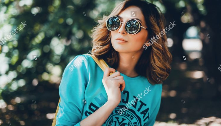 stock-photo-close-up-lifestyle-fashion-portrait-of-young-hipster-woman-walking-at-park-travel-with-backpack-335467001
