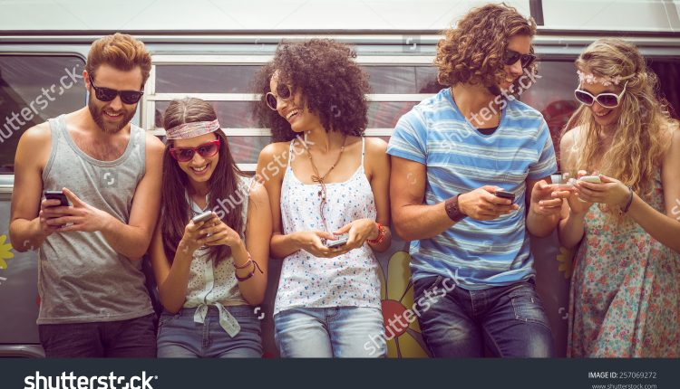 stock-photo-hipster-friends-using-their-phones-on-a-summers-day-257069272