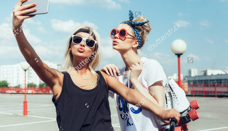 stock-photo-two-young-women-taking-selfie-with-mobile-phone-swag-teen-girls-outdoor-lifestyle-portrait-292530650