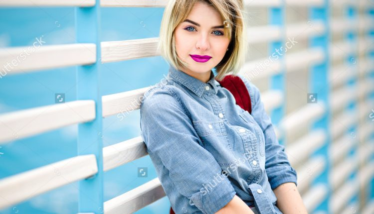 stock-photo-close-portrait-of-a-smiling-girl-with-short-blond-hair-bright-pink-lips-and-nude-make-up-leaning-428797141