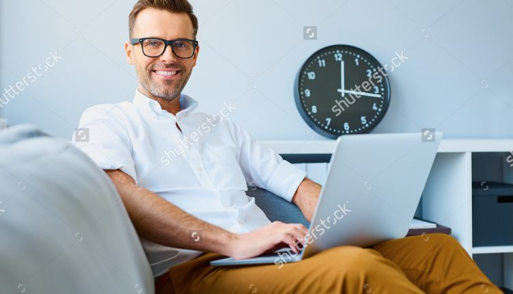 stock-photo-happy-man-wearing-glasses-sitting-with-laptop-relaxed-on-sofa-424633237