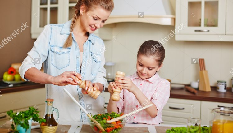 stock-photo-cute-girl-and-her-mother-adding-salt-or-spices-into-bowl-with-fresh-vegetable-salad-273673481