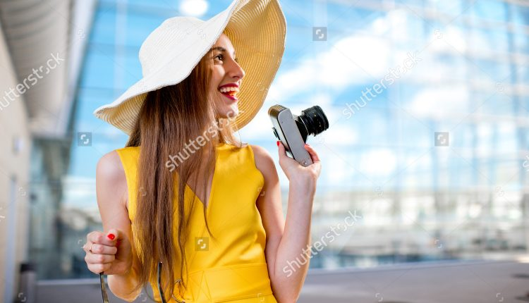 stock-photo-young-traveling-woman-with-photo-camera-and-panama-dressed-in-yellow-dress-standing-in-front-of-the-188889353
